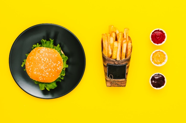 Flat lay hamburger with fries and sauces Free Photo