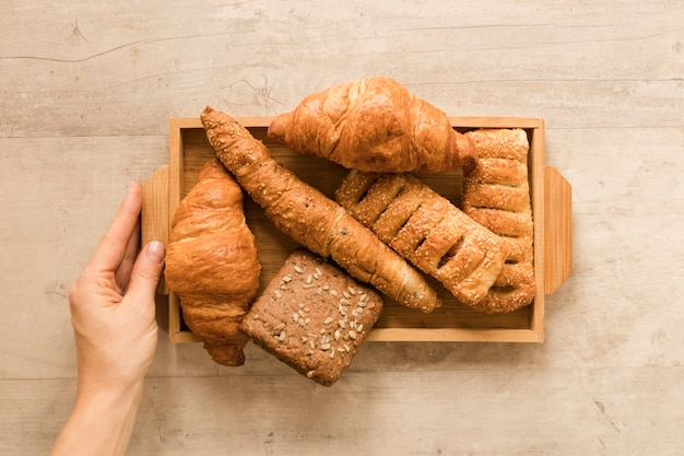 Flat lay hand holding mix of pastry in wooden box Free Photo