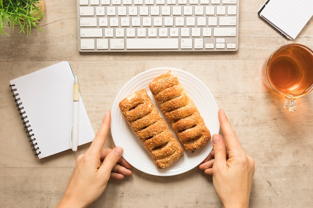 Flat lay hand holding plate of pastry with notebook Free Photo