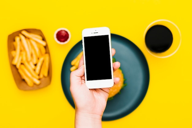 Flat-lay hand holding smartphone over plate with burger and fries Free Photo