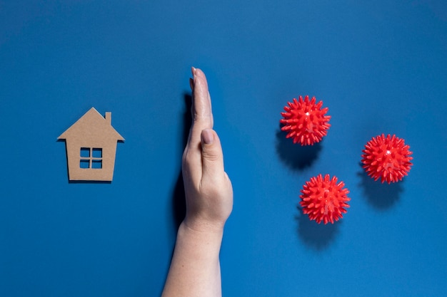 Flat lay of hand protecting house from viruses Free Photo