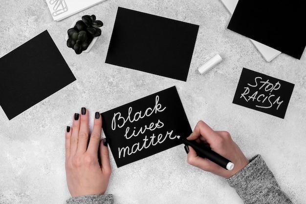 Piatto le mani che scrivono la vita nera importa sulla carta con la penna Foto Gratuite