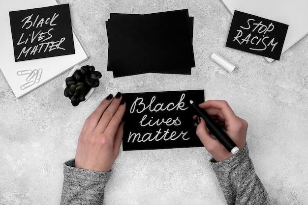Piatto le mani che scrivono vite nere sono importanti sulla carta Foto Gratuite