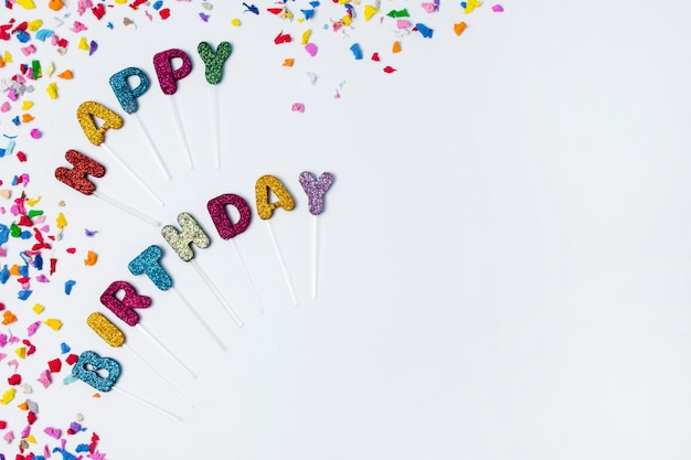 Flat lay happy birthday lettering on white background with copy space Free Photo