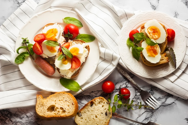 Flat lay hard boiled eggs with tomatoes and hotdog Free Photo