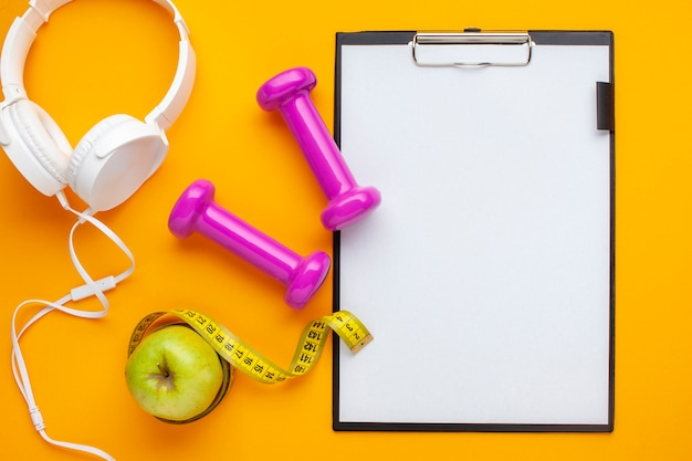 Flat lay headphones and clipboard on yellow background Free Photo