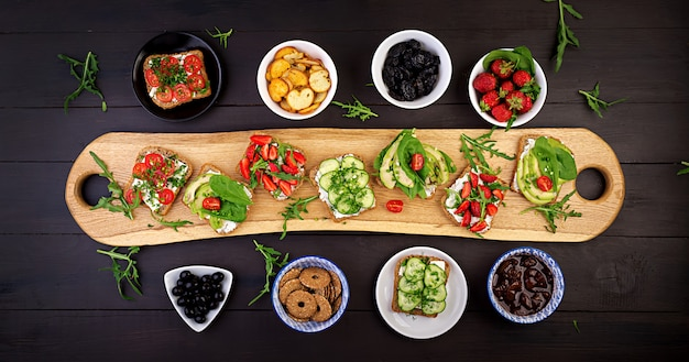 Flat lay of healthy vegetarian dinner table setting. sandwiches with tomato, cucumber, avocado, strawberry, herbs and olives, snacks. clean eating, vegan food Free Photo