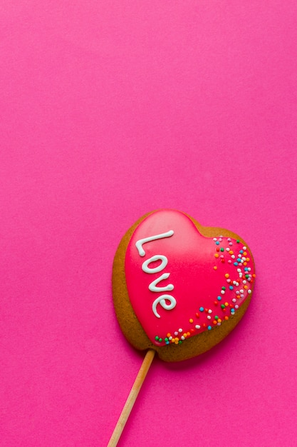 Flat lay of heart-shaped cookie on stick and copy space Free Photo