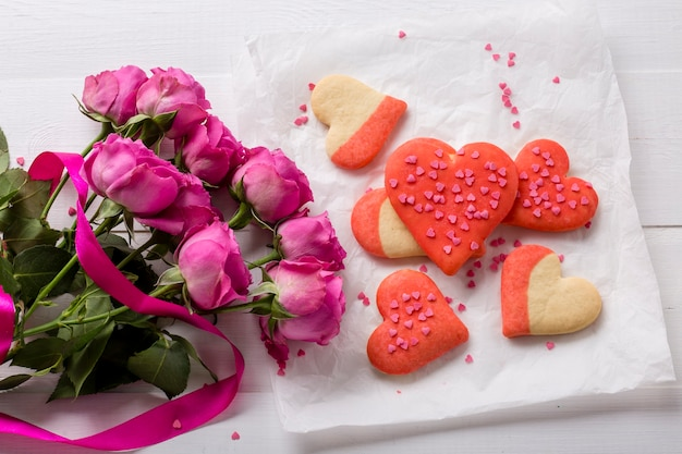 Flat lay of heart-shaped cookie with rose bouquet Free Photo