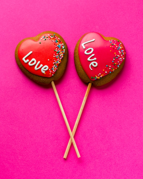 Flat lay of heart-shaped cookies on stick and pink background Free Photo