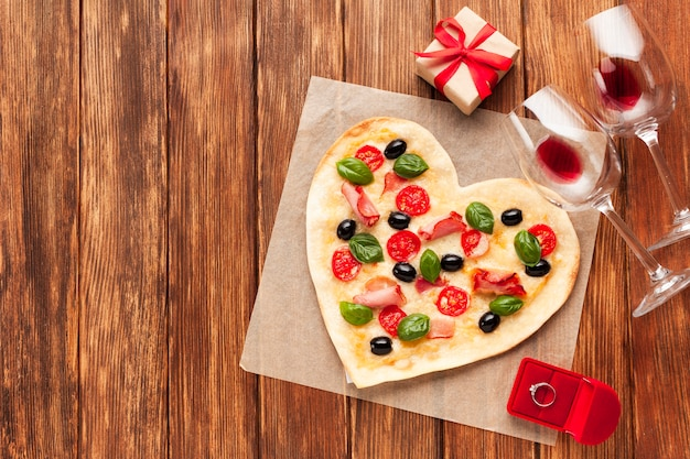 Flat lay heart shaped pizza with ring Free Photo