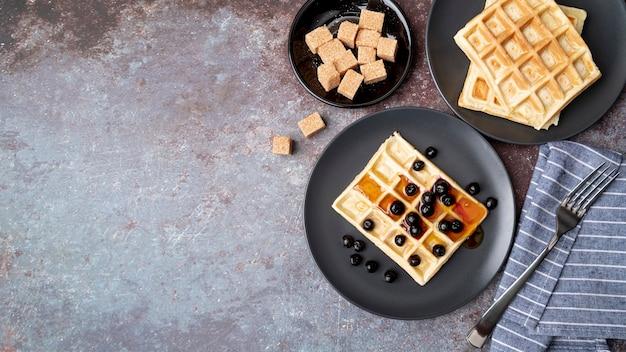 La disposizione piana delle cialde coperte di miele sul piatto con la frutta e copia lo spazio Foto Gratuite