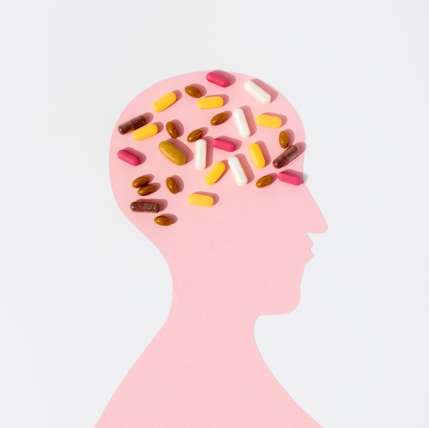 Flat lay of human shape with lots of pills on brain Free Photo