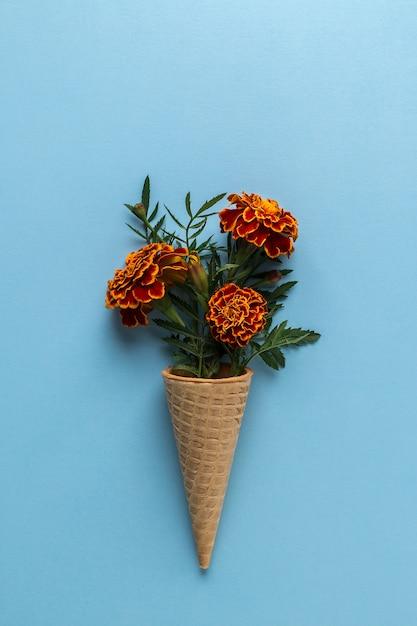Flat lay ice cream cone with of marigold flowers Premium Photo