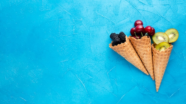Flat-lay ice cream cones with berries with copy space Free Photo