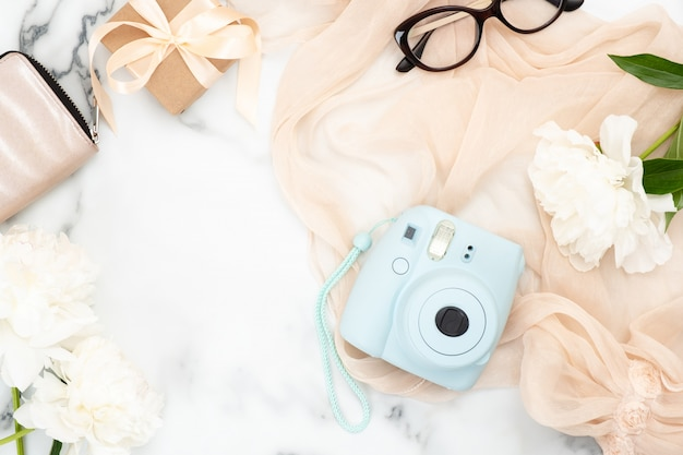 Flat lay instant film camera, glasses, purse, pastel pink woman scarf, white peony flowers Premium Photo