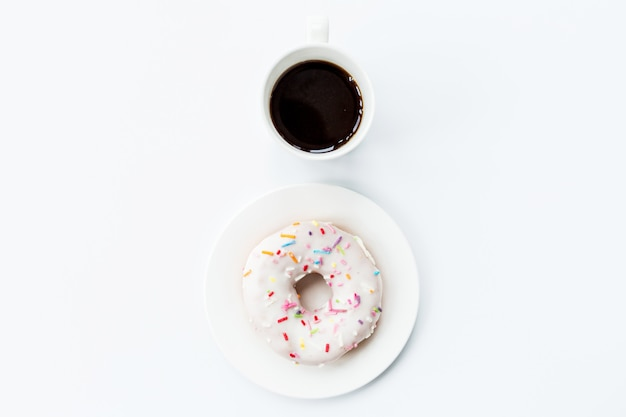 Flat lay items: coffee cup and donut lying on white background Premium Photo