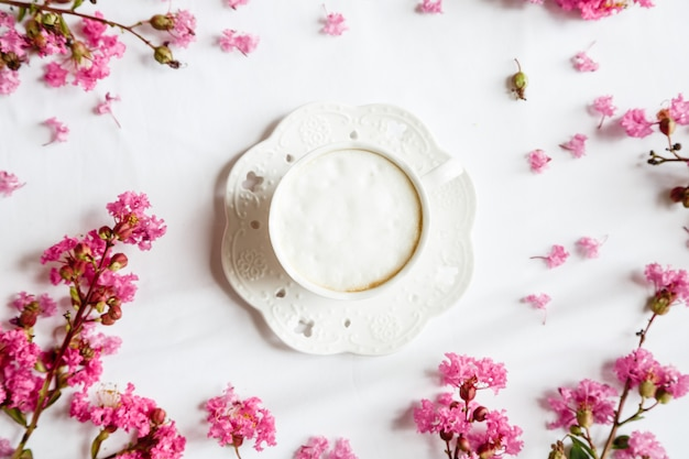 Flat lay items: coffee mug and pink flowers on white table Premium Photo