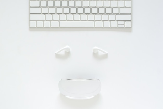 Flat lay of keyboard, earphone and mouse set as smiling face on white background for cyber monday online sale concept. Premium Photo