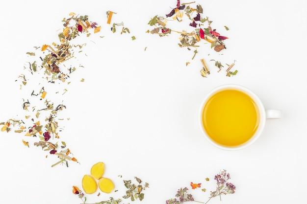 Плоский макет чашки зеленого чая с ассортиментом различных сухих чайных листьев и имбиря на белом фоне, копией пространства для текста Premium Фотографии
