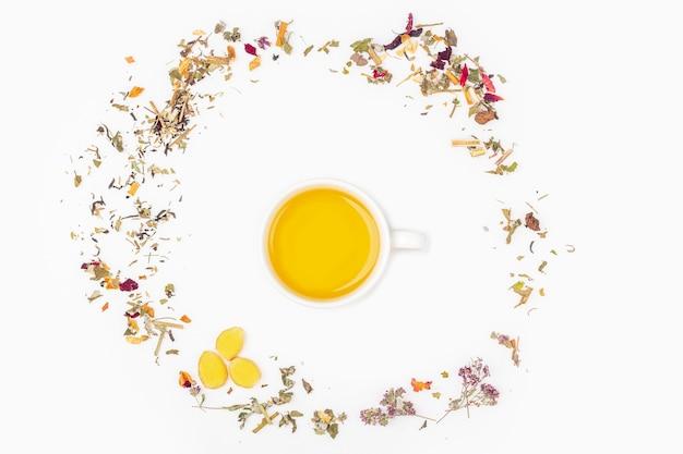 Плоская планировка чашки зеленого чая с ассортиментом различных сухих чайных листьев и имбиря Premium Фотографии