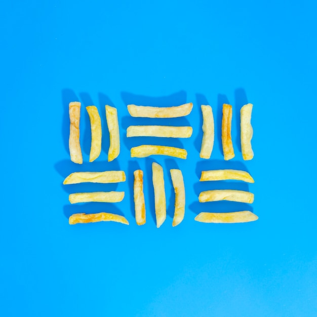 Flat lay of lined fries on blue background Free Photo