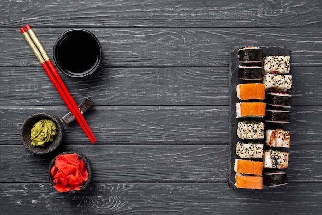 Flat lay maki sushi assortment on slate with chopsticks Free Photo