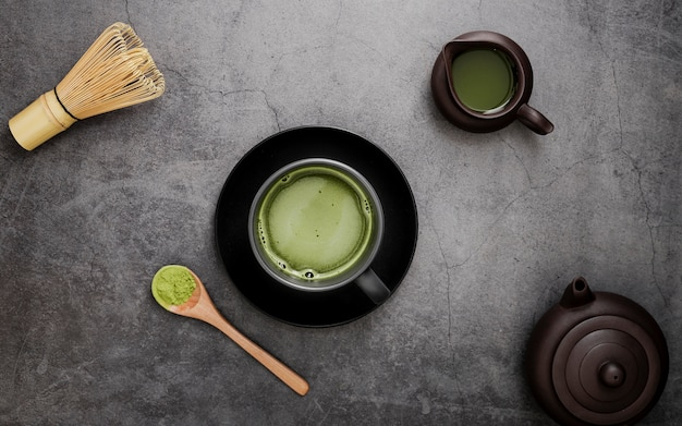 Flat lay of matcha tea in cup on plate with bamboo whisk Free Photo