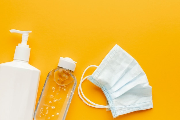 Lay piatto della maschera medica con bottiglia di liquido e disinfettante per le mani Foto Gratuite