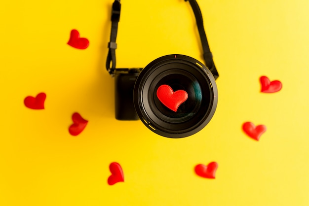 Flat lay of mirrorless camera with lens and love red hearts on yellow background Premium Photo