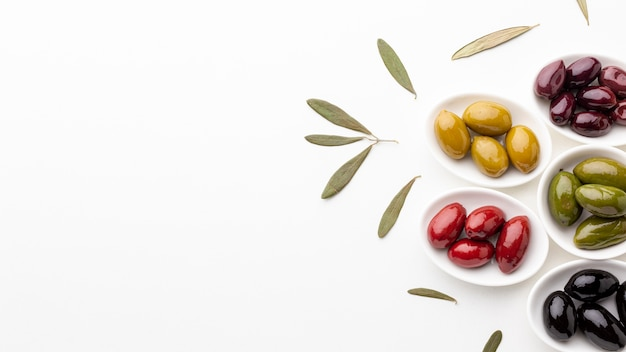 Flat lay mix of black red green purple yellow olives and oil with copy space Free Photo