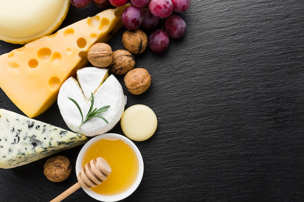 Flat lay mix of cheese walnuts and honey with copy space Free Photo