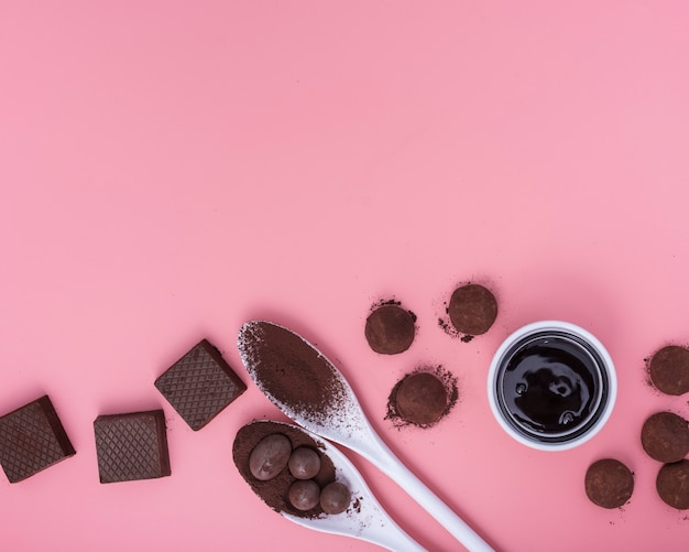 Flat lay mix of chocolate sweets on pink background with copy space Free Photo