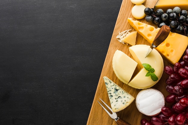 Flat lay mix of gourmet cheese and grapes on cutting board with copy space Free Photo