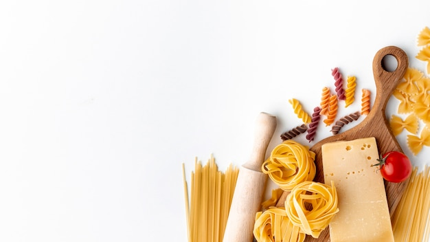 Flat lay mix of uncooked pasta and hard cheese with copy space Free Photo