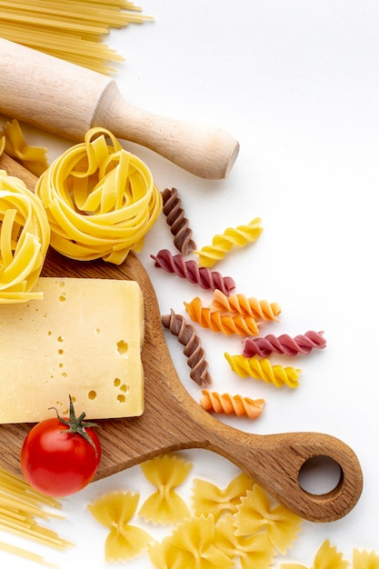 Flat lay mix of uncooked pasta with tomatoes and hard cheese Free Photo