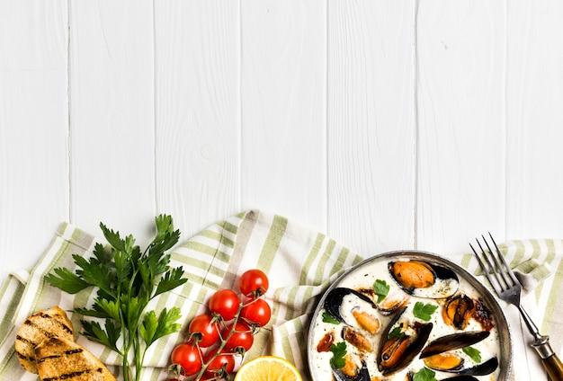 Flat-lay mussels in white sauce and sides on tablecloth with copyspace Free Photo