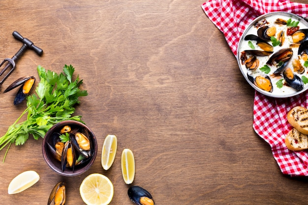 Flat-lay mussels in white sauce on tablecloth with copyspace Free Photo