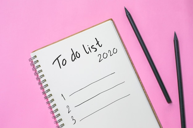 Flat lay new year to do list on blank notebook, planning wish 2020 concept Premium Photo
