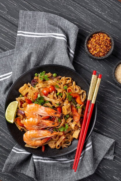 Flat lay noodles with vegetables and chicken with chopsticks and spices Free Photo