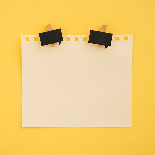 Flat lay of note and paper clips with yellow background Free Photo
