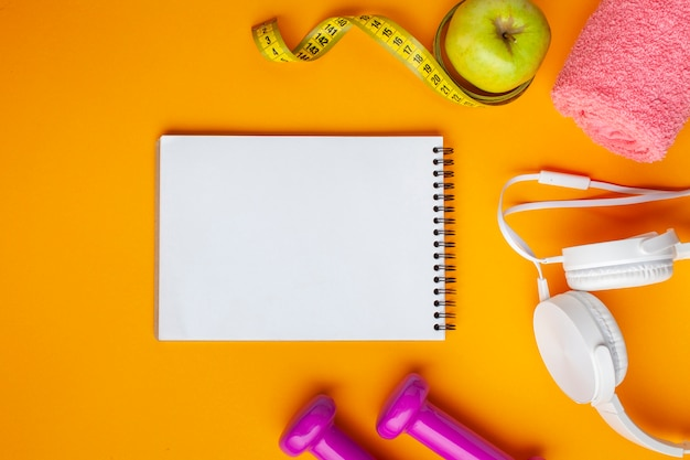 Flat lay notebook and apple on yellow background Free Photo