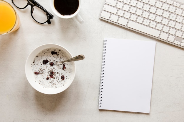 Flat lay notebook and bowl with yogurt raisins and chia seeds Free Photo
