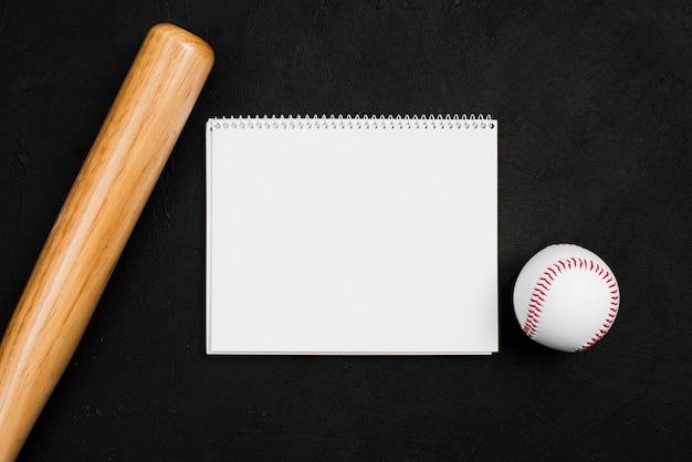 Flat lay of notebook with baseball and bat Free Photo