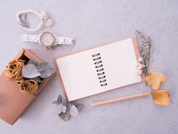 Flat lay of notebook, wristwatch and bracelet on vintage background with copy space Premium Photo