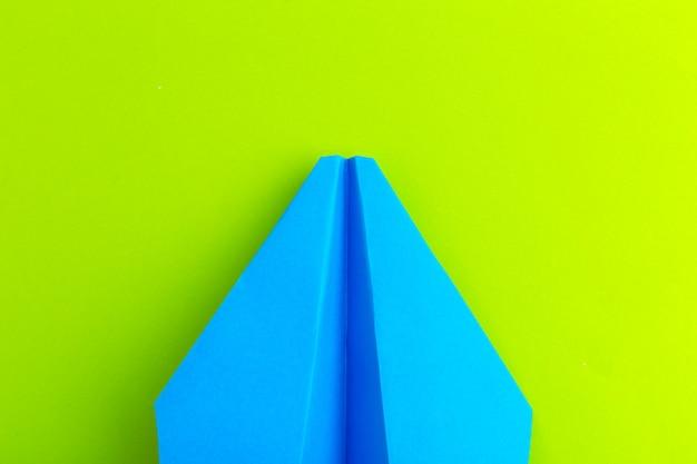 녹색 파스텔 색상 배경에 종이 비행기의 평면 배치 프리미엄 사진