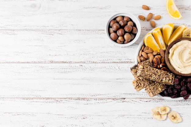 Плоская раскладка ассортимента ореха на тарелке с зерновыми батончиками Бесплатные Фотографии