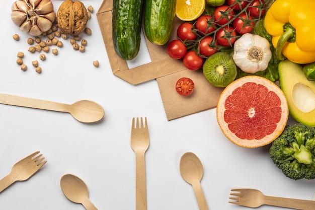Плоская планировка ассортимента овощей с бумажным пакетом и деревянными столовыми приборами Бесплатные Фотографии