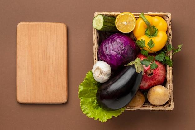 Плоская корзина со свежими овощами с разделочной доской Бесплатные Фотографии