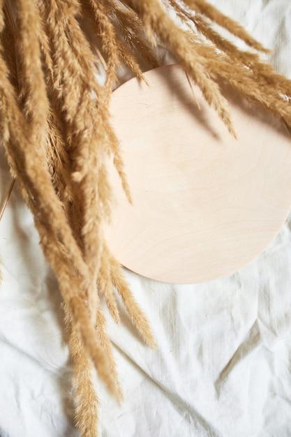 Плоская планировка бежевой камышовой травы пампасов на фоне белой текстильной льняной скатерти, красивый узор с нейтральными цветами, минимальная, стильная, трендовая концепция, вид сверху Premium Фотографии